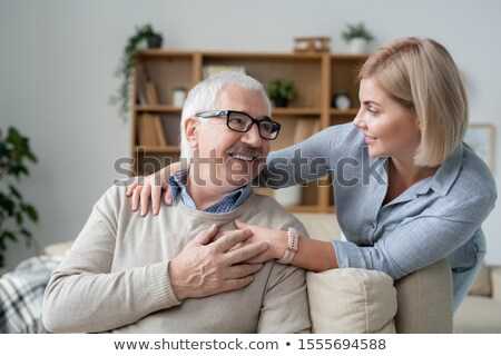Restful senior man on couch looking at his young daughter standing near by Stock photo © pressmaster