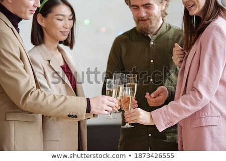 happy colleagues toasting for christmas with champagne while enjoying party stock photo © pressmaster