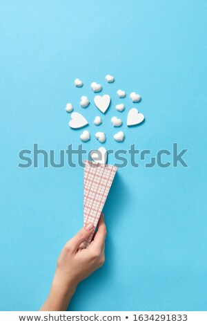 Woman's hand with paper cone of small plaster hearts. Stock photo © artjazz
