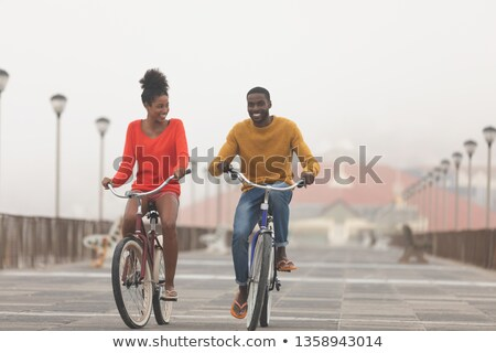 Front view of Multi-ethnic couple riding bicycle at promenade on a sunny day Stock photo © wavebreak_media