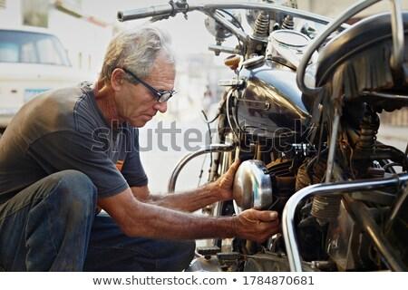 Senior Man Examining His Motorcycle And Fixing Engine Stock photo © diego_cervo