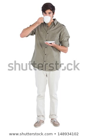 portrait of a young man drinking coffee and looking at camera stock photo © hasloo