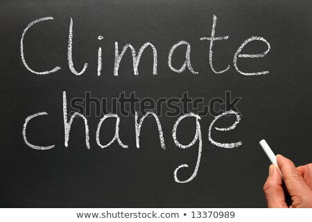 A teacher writing Climate change on a blackboard. Stock photo © latent