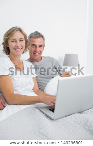 middle aged couple with a laptop on their bed stock photo © photography33