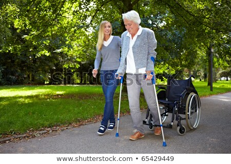 Young woman helping elderly person to walk with a crutch Stock photo © photography33