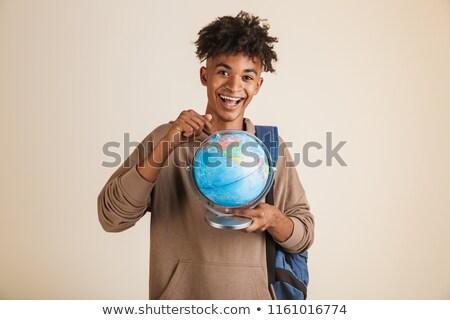boldog · férfi · mutat · ujj · földgömb · fiatalember - stock fotó © stockyimages