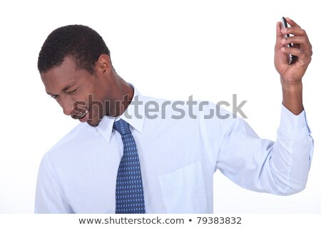 excited black man wincing and holding a cell phone in his hand Stock photo © photography33