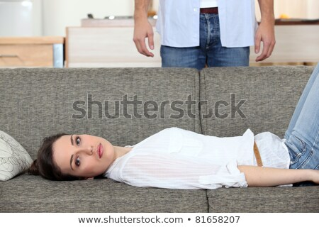 Woman laying on couch husband stood behind Stock photo © photography33