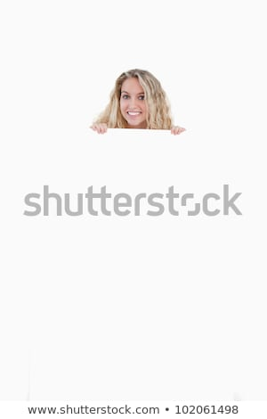 Young woman hiding her body behind a blank poster against a white background stock photo © wavebreak_media