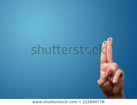 feliz · rosto · sorridente · dedos · olhando · vazio · azul - foto stock © ra2studio