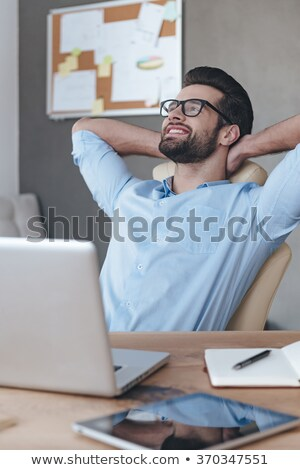 pensive young business man behind laptop looks away stock photo © feedough
