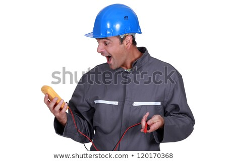 Stock photo: Man shocked by reading from voltmeter