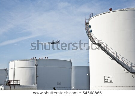 white tanks in tank farm with blue sky and approaching aircraft Stock photo © meinzahn