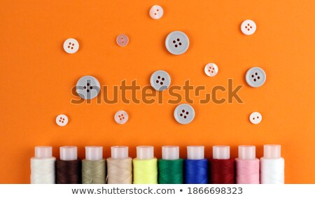 Bright sewing buttons and threads on gray fabric Stock photo © tetkoren