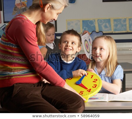 Female Teacher In Primary School Teaching Children To Tell Time  Stock photo © monkey_business