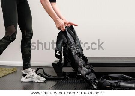 young woman putting on electro muscular stimulation ems exercise training costume stock photo © nejron