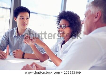Többnemzetiségű üzleti csapat megbeszélés fókusz fiatalember boldog Stock fotó © deandrobot