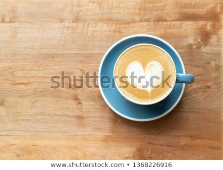 frothy top of a cup of coffee with heart pattern stock photo © smartin69