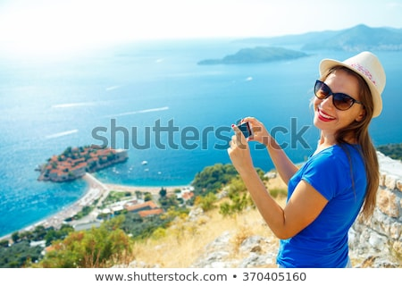 Girl in hat making photos of the Adriatic sea by the smartphone Stock photo © vlad_star