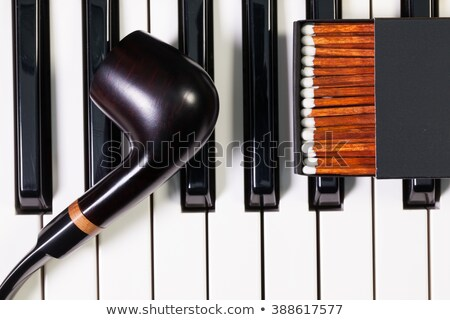 Piano keyboard and  luxury tobacco pipe Stock photo © CaptureLight