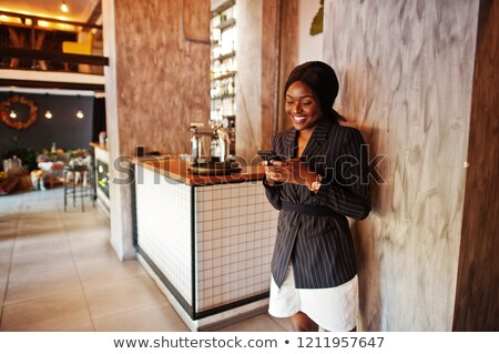 beautiful stylish girl talking on the phone in cafe stock photo © deandrobot