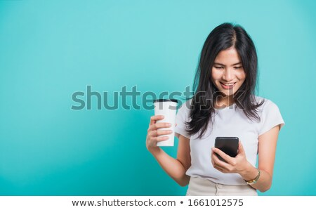 Woman with coffee, looking at her phone Stock photo © IS2