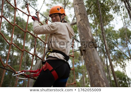 woman wearing safety helmet climbing on a rope fence in the forest stock photo © wavebreak_media