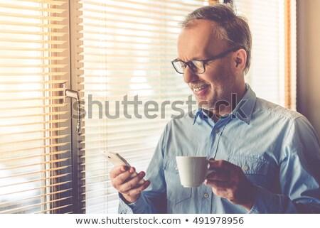 man using mobile his phone while drinking coffee stock photo © wavebreak_media