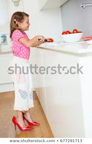 Girl cutting tomatoes in high heels Stock photo © IS2