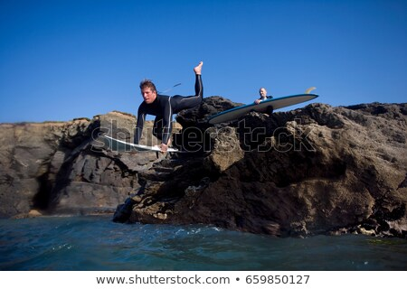 Man jumping onto surfboard Stock photo © IS2