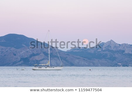 Seascape with a sailing yacht and a full moon over the mountain Stock photo © Kotenko