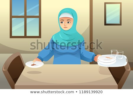 Muslim Woman Cleaning Up Dining Table After Dinner Stockfoto © Artisticco