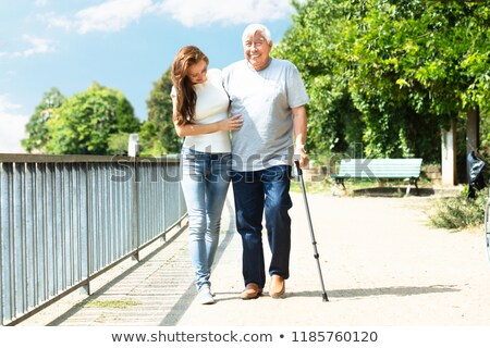 Woman Assisting Her Father While Walking In Park Stock photo © AndreyPopov