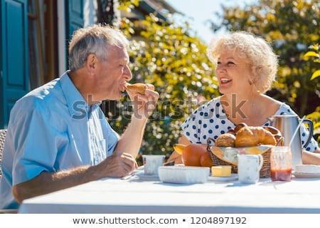 Senior woman and man having breakfast sitting in their garden outdoors Stock photo © Kzenon