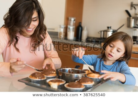 happy mother and daughter cooking cupcakes at home Stock photo © dolgachov