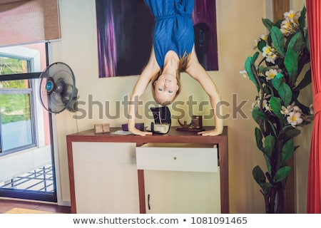 A woman is standing on his hands upside down in the living room stock photo © galitskaya