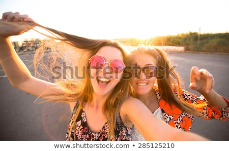 young beautiful women friends make selfie by mobile phone stock photo © deandrobot