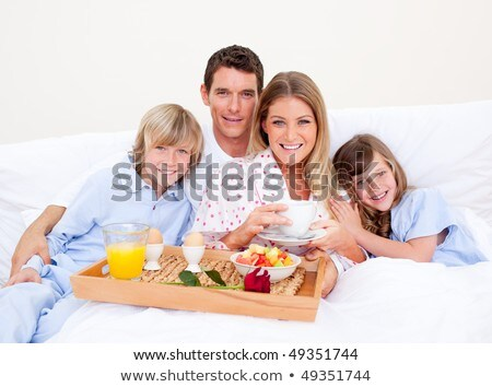 Jolly woman having breakfast at home Stock photo © Lopolo