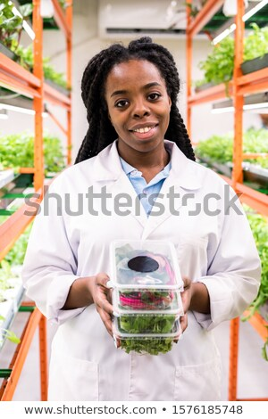 Successful African female agronomist holding stack of plastic containers Stock photo © pressmaster