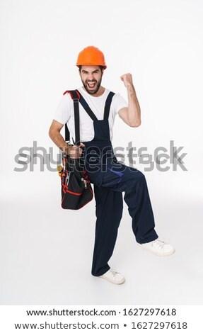 Optimista fiatalember építész tart táska felszerlés Stock fotó © deandrobot