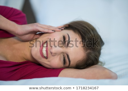 Closeup portrait of young pretty girl laying on her bed Stock photo © HASLOO