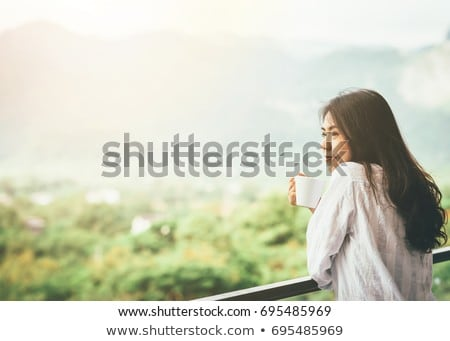 woman holding hot cup and smiles stock photo © artjazz