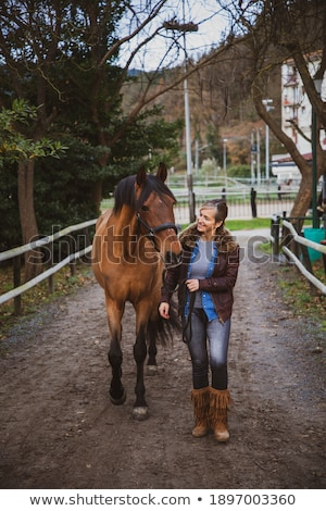 Young cowgirl in shorts preparing saddle for a ride Stock photo © deandrobot