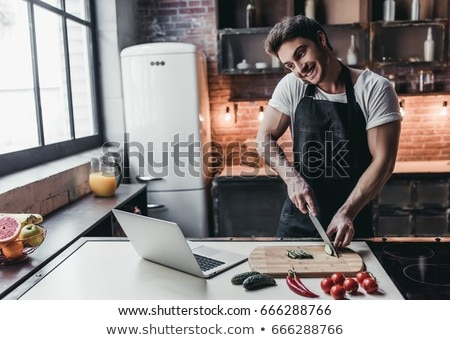 Man in kitchen with laptop and vegetables Stock photo © photography33