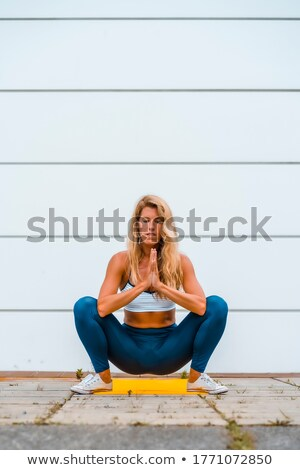 Fit female model in crouching posture Stock photo © stockyimages