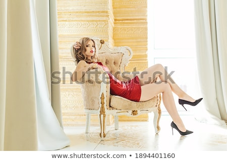 glamorous woman with long hair sitting in luxurious golden armch stock photo © victoria_andreas