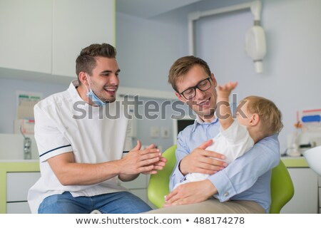 father and son visiting dentist at dental clinic Stock photo © dolgachov