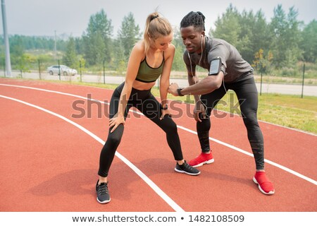 Young athlete showing time to active girl while both standing on start line Stock photo © pressmaster