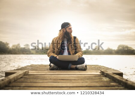 Man looking his laptop by the lake Stock photo © photography33