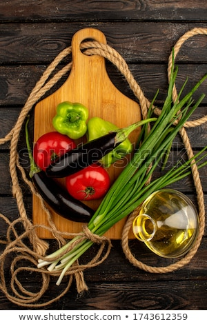 Fresh healthy vegetarian vegetables salad with tomatoes and cucumber, red onion and spinach in black Stock photo © DenisMArt